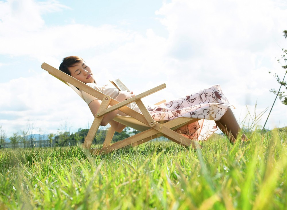 Young Woman Sleeping on Lawn Chair